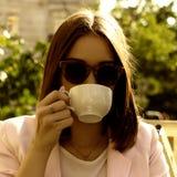 Den unga nätta flickan dricker en kopp av den varma drycken som är utomhus- Royaltyfri Foto