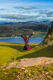 Den unga nätta flickan hoppar från vaggar lyckligt i det Front Of Spectacular Landscape Of Applecross passerandet i Skottland arkivfoton