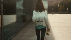 Den unga nätta flickan i exponeringsglas går outdoos med böcker i händer och leenden arkivfilmer