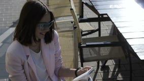 Den unga nätta flickan läser en bok som är utomhus- lager videofilmer