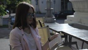 Den unga nätta flickan läser en bok som är utomhus- arkivfilmer