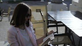 Den unga nätta flickan läser en bok som är utomhus- stock video