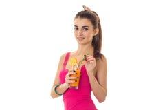 Den unga nätta flickan med härligt leende dricker den nya orange coctailen som ler på kameran som isoleras på vit bakgrund Royaltyfria Foton