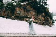 Den unga nätta flickan väntar på hennes vän i mitt av bergen som täckas med snö Arkivfoto