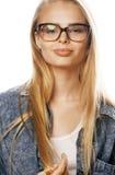 Den unga nätta flickatonåringen i exponeringsglas på vit isolerade den moderna hipsteren för blont hår Royaltyfria Bilder