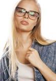 Den unga nätta flickatonåringen i exponeringsglas på vit isolerade den moderna hipsteren för blont hår Arkivbilder