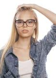 Den unga nätta flickatonåringen i exponeringsglas på vit isolerade den moderna hipsteren för blont hår Arkivbild