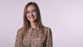 Den unga nätta inspirerade kvinnan är driftigt hår och att hålla ögonen på på kameran och att le, vit bakgrund arkivfilmer
