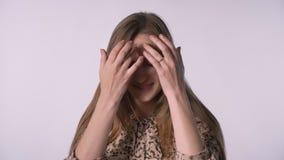 Den unga nätta kvinnan är driftigt hår och att hålla ögonen på på kameran och att le, vit bakgrund stock video