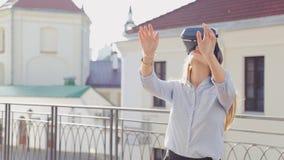 Den unga nätta kvinnan använder utomhus- exponeringsglas för teknologi för cyberspace för vrvirtuell verklighethörlurar med mikro lager videofilmer