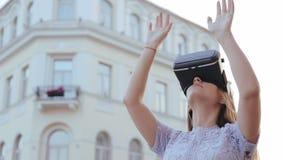 Den unga nätta kvinnan använder utomhus- exponeringsglas för teknologi för cyberspace för vrvirtuell verklighethörlurar med mikro arkivfilmer