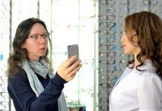 Den unga nätta kvinnan försöker ögonexponeringsglas på en eyewear shoppar på med hjälp av shoppar assistenten och aktier i social royaltyfria bilder