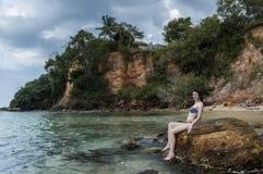Den unga nätta kvinnan i bikinin som sitter på, vaggar på stranden royaltyfri foto