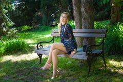 Den unga nätta kvinnan i elegant kort klänning sitter på träbänk in Royaltyfri Bild