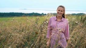 Den unga nätta kvinnan i skjorta poserar i sommarvetefält stock video