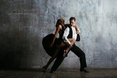 Den unga nätta kvinnan i svart klänning och mannen dansar tango royaltyfri bild