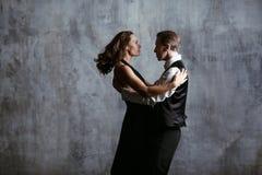 Den unga nätta kvinnan i svart klänning och mannen dansar tango arkivfoton