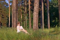 Den unga nätta kvinnan i vit ler och sitter i grönt gräs Royaltyfri Bild