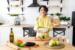 Den unga nätta kvinnan klipper en avokado på ett träsalladbräde matlagning Förberedelse av sallad för ny grönsak royaltyfri bild