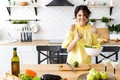 Den unga nätta kvinnan klipper en avokado på ett träsalladbräde matlagning Förberedelse av sallad för ny grönsak royaltyfria foton