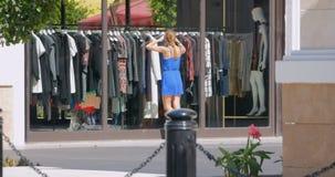 Den unga nätta kvinnan ser in i shoppar fönstret för ` s stock video