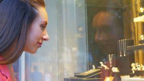 Den unga nätta kvinnan ser smycken i shoppar fönstret arkivfilmer