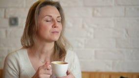 Den unga nätta kvinnan sitter i kafé med kopp te eller kaffe och att svälja Lycklig flicka som dricker drycken och ser lager videofilmer