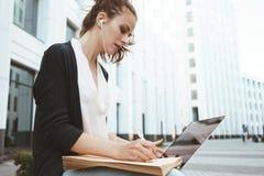 Den unga nätta kvinnan skriver med en penna på pappers- dokument och information om sökande i internet på bärbara datorn i affärs Royaltyfri Bild