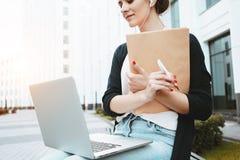 Den unga nätta kvinnan skriver med en penna på pappers- dokument och information om sökande i internet på bärbara datorn i affärs Arkivfoton