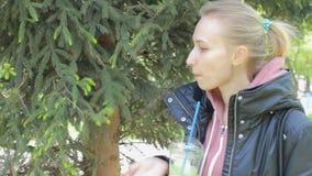 Den unga nätta kvinnan som in går, parkerar och att dricka den gröna grönsakdetoxsmoothien arkivfilmer