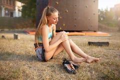 Den unga nätta kvinnan som har en trauma med knäet, efter klättra övning, vaggar på väggen Den upprivna kvinnliga klättraren har  arkivfoton
