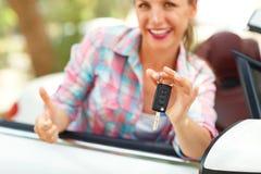 Den unga nätta kvinnan står nära den konvertibla bilen med Royaltyfri Fotografi