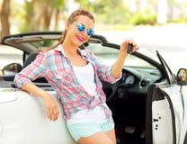 Den unga nätta kvinnan står nära den konvertibla bilen med Arkivfoton