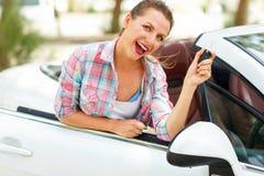 Den unga nätta kvinnan står nära den konvertibla bilen med Arkivbild