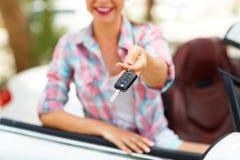 Den unga nätta kvinnan står nära den konvertibla bilen med Fotografering för Bildbyråer