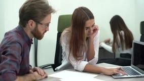 Den unga nätta kvinnan visar att hennes kollega ett projekt på en dator och de diskuterar affärsstrategi eller plan idérikt stock video