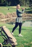 Den unga nätta kvinnliga golfspelaren lyckas, i att slå för boll Arkivfoto