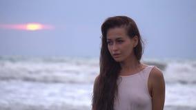 Den unga nätta kvinnlign med långt mörkt hår i vit swimwear i ultrarapid ser bort på solnedgånghavstranden lager videofilmer