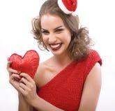 Den unga nätta lyckliga le brunettkvinnan på jul i santas den röda hatten isolerade hjärtagåvan, livsstilfolkbegrepp Arkivbilder