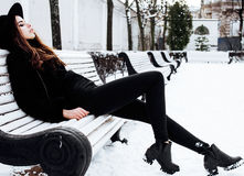 Den unga nätta moderna hipsterflickan som väntar på bänk på vintersnö, parkerar bara, livsstilfolkbegreppet Royaltyfria Foton