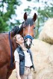 Den unga nätta ryttaren för den tonårs- flickan kramar hennes favorit- häst royaltyfri bild
