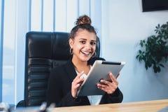 Den unga nätta smarta affärsflickan arbetar i kontoret Under detta tog arbetade hon minnestavlan och på den arkivfoto