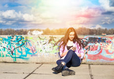 Den unga nätta tonårs- kvinnan använder hennes telefon i stad parkerar nära floden royaltyfri bild