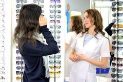 Den unga n?tta kvinnan f?rs?ker solexponeringsglas p? en eyewear shoppar p? med hj?lp av shoppar assistenten royaltyfri bild