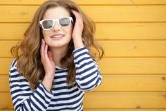 Den unga n?tta stilfulla le kvinnan som g?r selfiefotoet p? kamera i stad, parkerar, den positiva, emotionella b?rande gula ?verk royaltyfri foto