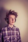 Den unga nerden lyssnar musik till och med hörlurar Royaltyfri Bild