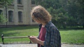 Den unga nerdy studenten med långt lockigt hår som går och skriver på telefonen, parkerar nära universitet eller gatan nära högsk stock video