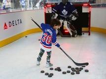 Den unga New York Rangersfanen som skjuter pucken för kommandosoldater, kryddar öppningsmatchen på Madison Square Garden i NYC Arkivfoto