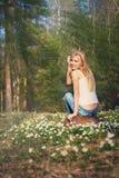 Den unga nätta blonda kvinnan på en äng blommar Arkivbilder