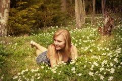 Den unga nätta blonda kvinnan på en äng blommar Royaltyfria Bilder